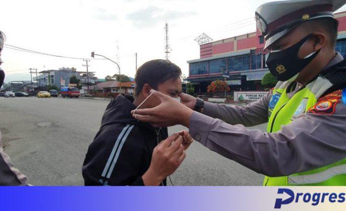 petugas satlantas memakaikan masker